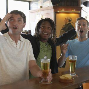 Three men drinking at bar, cheering and looking upwards